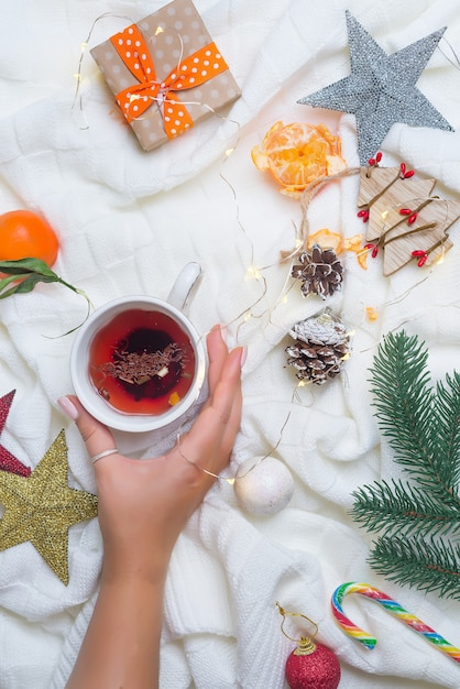 Femme, tenue, mains, chaud, thé noël, à, canne bonbon, contre, décorations Photo Premium