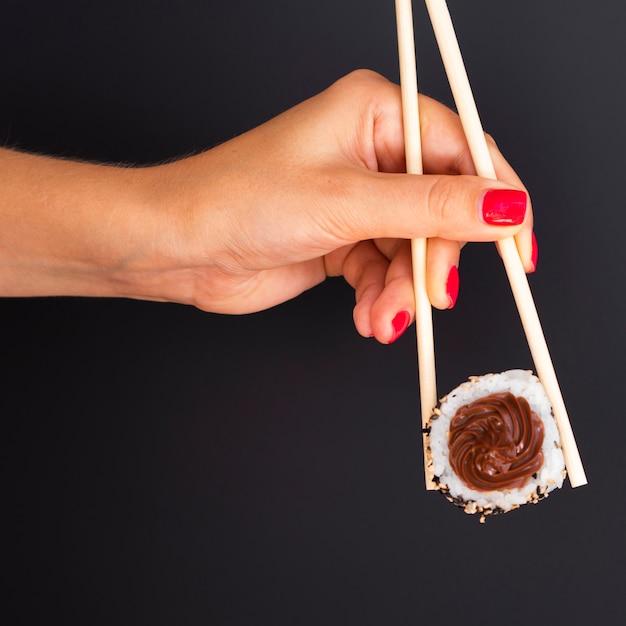 Femme, tenue, paire, baguettes, sushi, rouleau, fond noir Photo gratuit