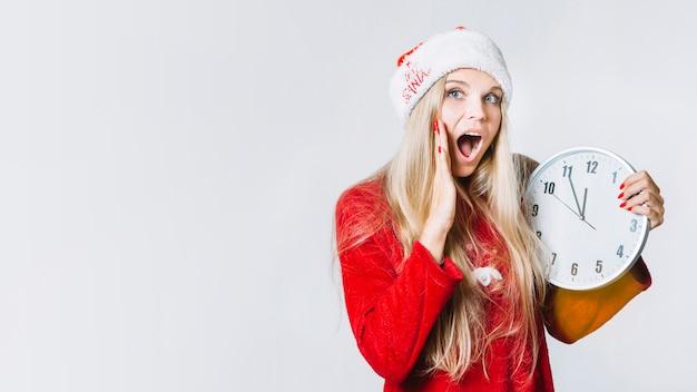 Femme en tenue rouge tenant l'horloge dans les mains Photo gratuit