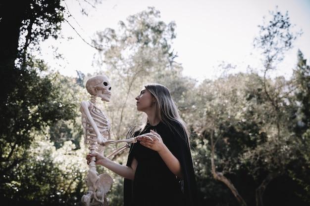 Femme En Tenue De Sorcier à L'écoute Du Squelette Photo gratuit
