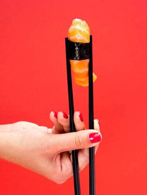 Femme, tenue, sushi, fond rouge Photo gratuit