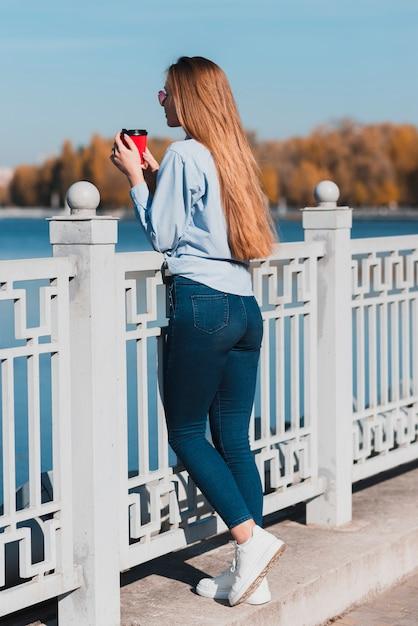 Femme, tenue, tasse à café, reposer, balustrade Photo gratuit