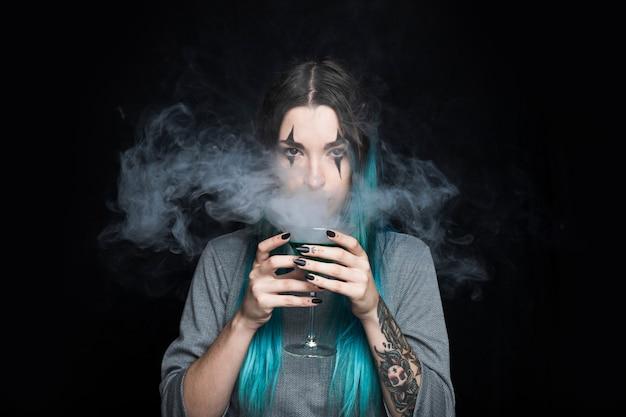 Femme, tenue, verre, gobelet, à, liquide vert, et, fumée Photo gratuit