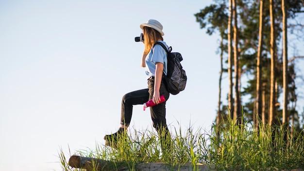 Femme avec thermos en prenant des photos Photo gratuit