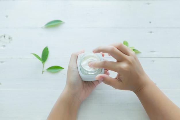 Femme tient un pot avec une crème cosmétique dans ses mains Photo gratuit