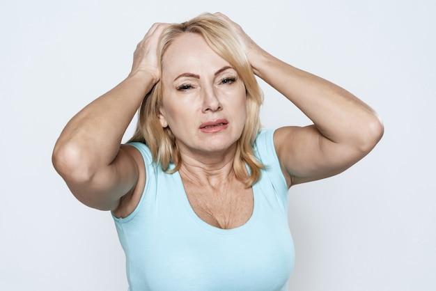 Une femme tient ses mains à sa tête Photo Premium