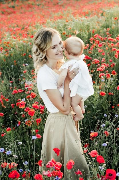 Une femme tient son bébé et sourit Photo gratuit