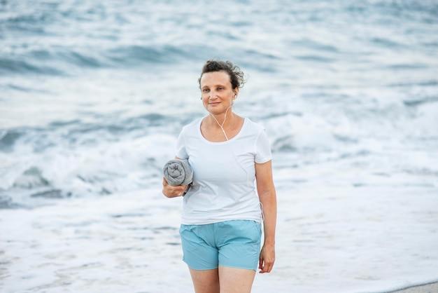 Femme De Tir Moyen Tenant Une Serviette Photo Premium