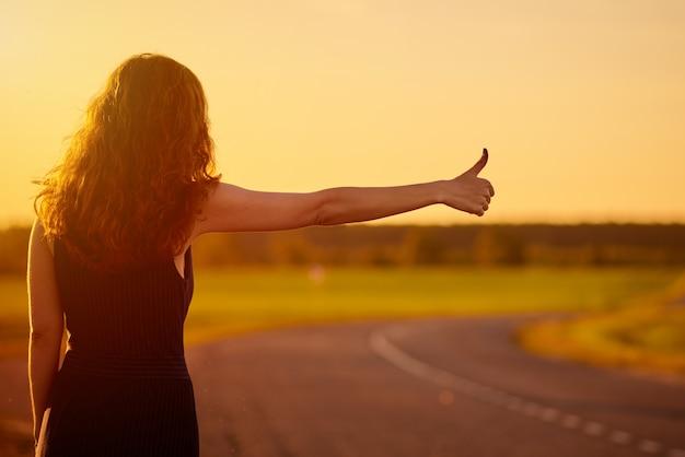 Femme de tourisme en attente de voiture sur la route en plein air au coucher du soleil Photo Premium