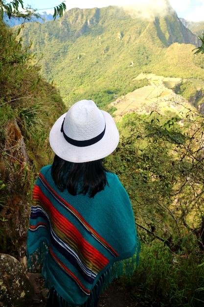 Femme touriste admirant la vue sur la citadelle du machu picchu depuis la montagne huayna picchu, cusco, urubamba, pérou. Photo Premium