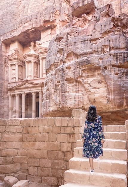 Femme touriste en robe de couleur et chapeau profitant du trésor, al khazneh dans l'ancienne ville de petra, jordanie Photo Premium