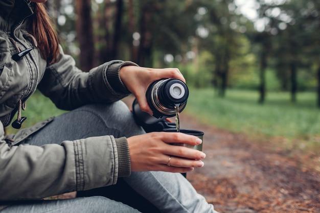 Femme touriste verse du thé chaud dans un thermos en forêt de printemps camping, voyages Photo Premium