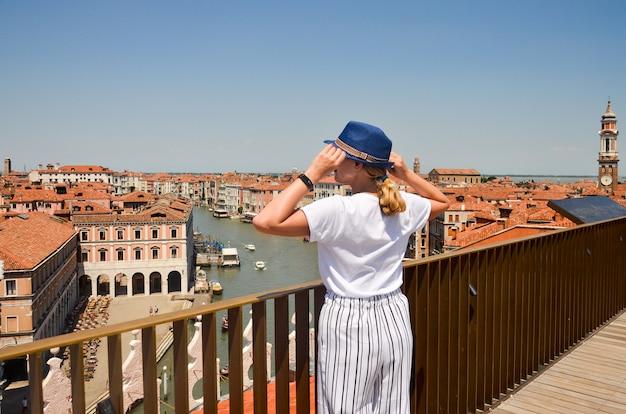 Femme Touriste Voyage En Italie. Vue Sur Grand Canal. Jeune Fille Avec Un Chapeau De Paille à Venise. Fille Voyageant à Venise à La Recherche Sur Le Toit Photo Premium