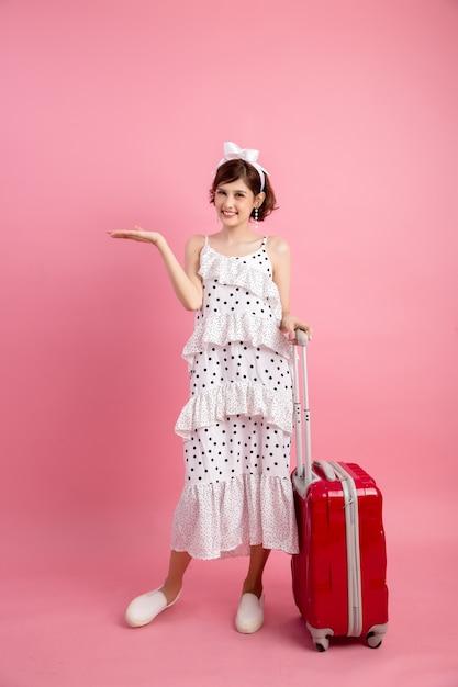 Femme touriste voyageur en vêtements décontractés avec valise de voyage isolé sur rose Photo gratuit