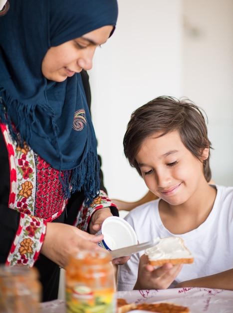 Femme traditionnelle musulmane avec fils à la cuisine Photo Premium