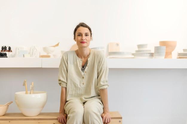 Femme en train de porter dans son atelier de table avec des objets faits à la main Photo Premium
