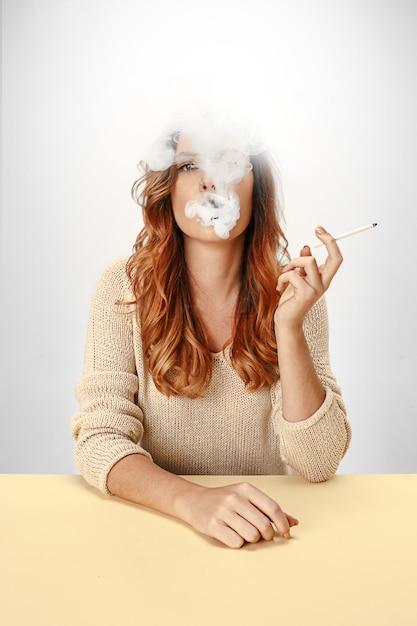Femme Tranquille Assise Et Fumant Au Repos à La Table. Photo gratuit