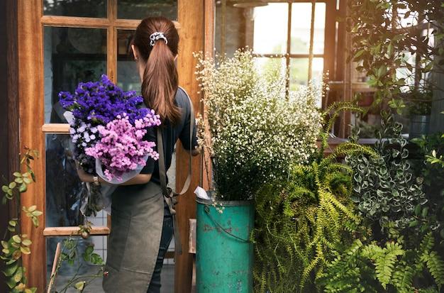 Femme travaillant dans son magasin de fleurs Photo gratuit