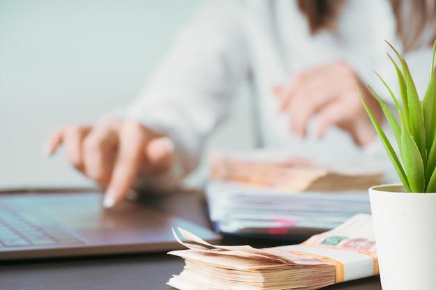 Femme travaillant à la main de bureau sur le clavier se bouchent. recompter de l'argent. Photo Premium