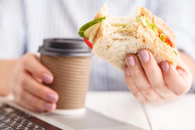 Femme Travaillant Et Mangeant Au Bureau Photo Premium