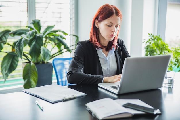 Femme travaillant avec un ordinateur portable dans un bureau