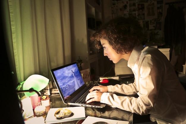 Femme travaillant sur un ordinateur portable la nuit Photo Premium