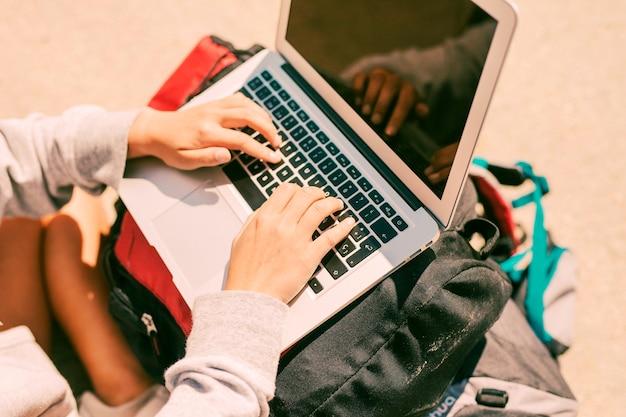 Femme travaillant sur un ordinateur portable placé sur des sacs à dos Photo gratuit