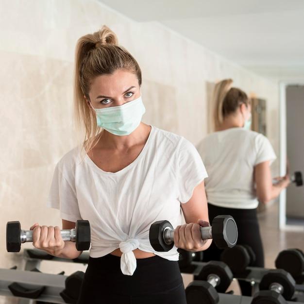 Femme Travaillant Avec Des Poids à La Salle De Sport Tout En Portant Un Masque Médical Photo Premium