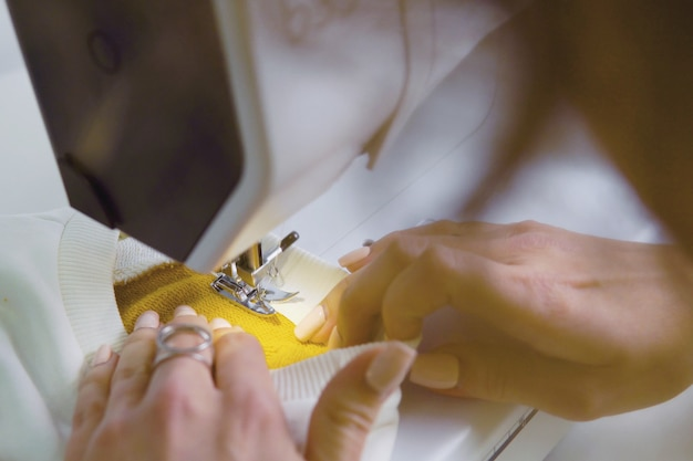 La femme travaille avec un morceau de tissu sur la machine à coudre Photo Premium