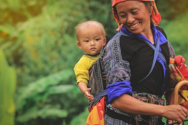 Femme de la tribu smling hmong portant son enfant dans son sac à dos à mu cang chai nord du vietnam Photo Premium