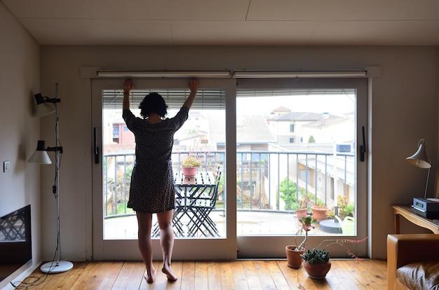 Une femme triste en regardant par la fenêtre à la maison Photo Premium