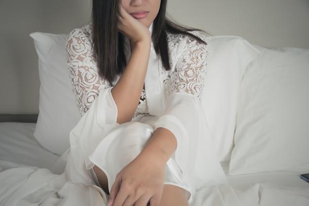 Femme triste solitaire et déprimée en chemise de nuit avec les mains sur le visage. Photo Premium