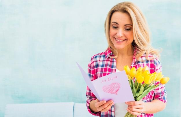 Femme, tulipes, lecture, carte voeux Photo gratuit