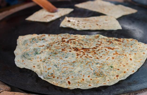 Une femme turque prépare gozleme - un plat traditionnel sous forme de pain plat farci de légumes verts et de fromage Photo Premium