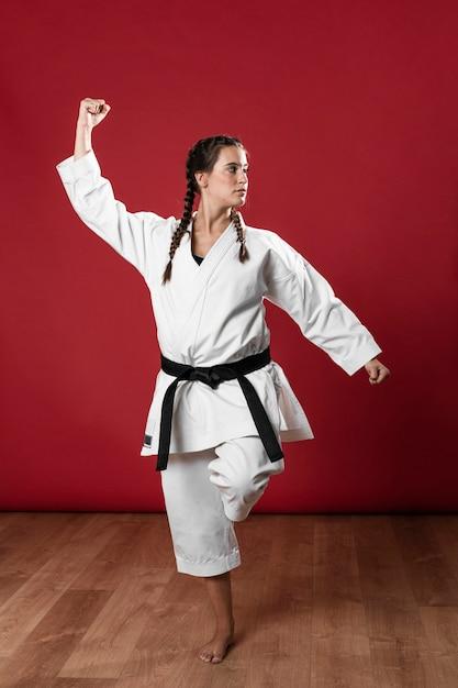 Femme en uniforme d'arts martiaux exerçant le karaté Photo gratuit