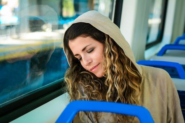 Femme urbaine dormant dans un train voyagent à côté de la fenêtre. Photo Premium