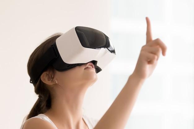 Femme utilisant des lunettes de réalité virtuelle pour des vidéos interactives Photo gratuit