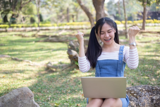 Femme utilisant un ordinateur portable levant les bras avec un regard de succès. Photo gratuit