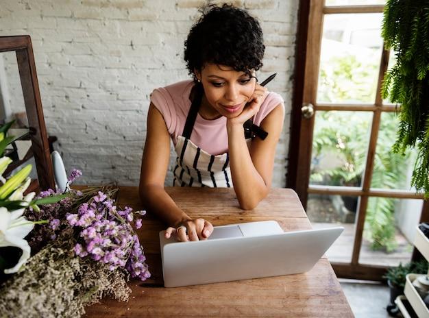 Femme utilisant un ordinateur portable en ligne flower shop Photo Premium