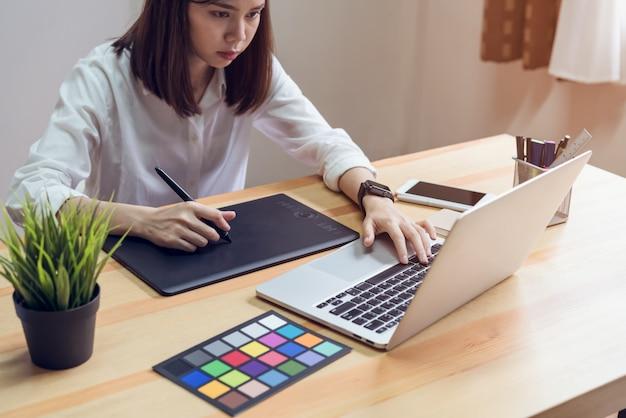 Femme Utilisant Un Ordinateur Portable Sur La Table Dans La Salle De Bureau, Pour Le Montage Graphique. Photo Premium