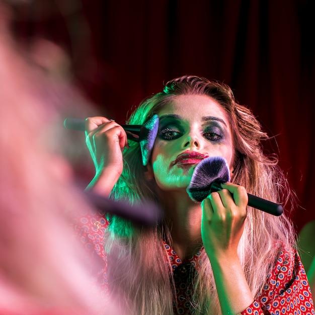 Femme utilisant plusieurs pinceaux sur son visage Photo gratuit