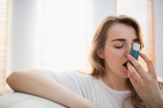 Femme utilisant son inhalateur sur un canapé dans le salon Photo Premium