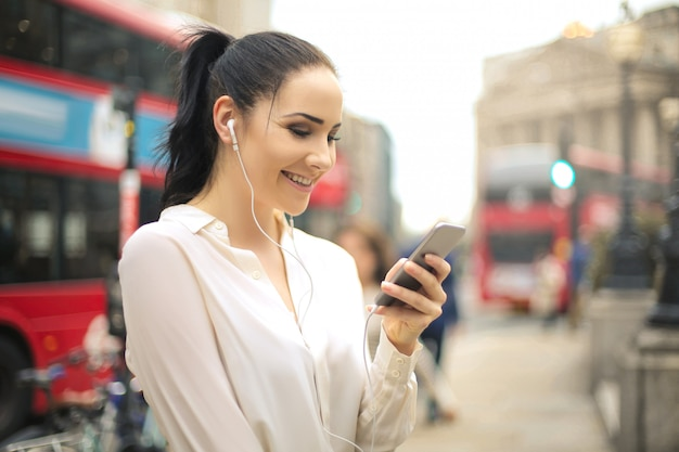 Femme utilisant son téléphone en écoutant avec des écouteurs Photo Premium