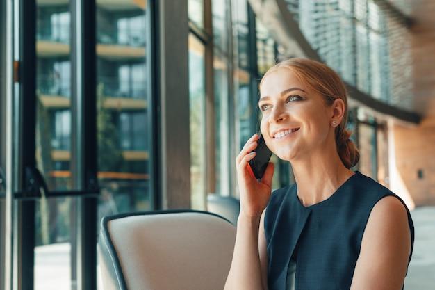 Femme utilisant un téléphone portable au bureau Photo Premium