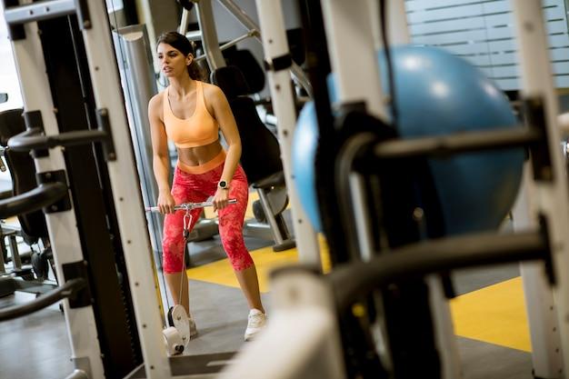 Femme, utilisation, barre droite, câble, tirer, poids, exercer, biceps, gymnase Photo Premium