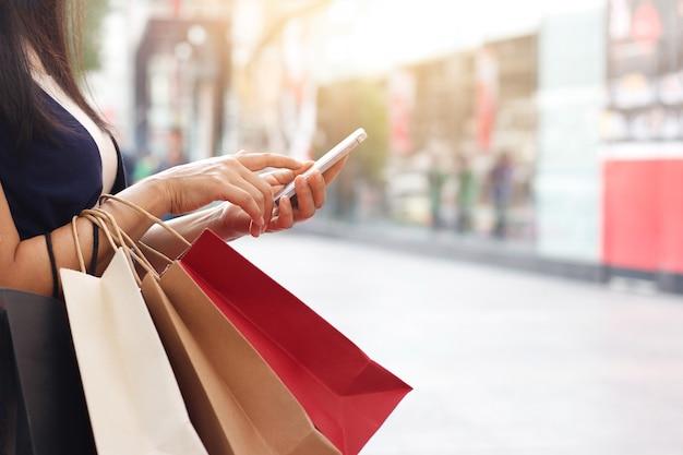 Femme, utilisation, smartphone, tenue, sac shopping, debout, fond, centre commercial Photo Premium