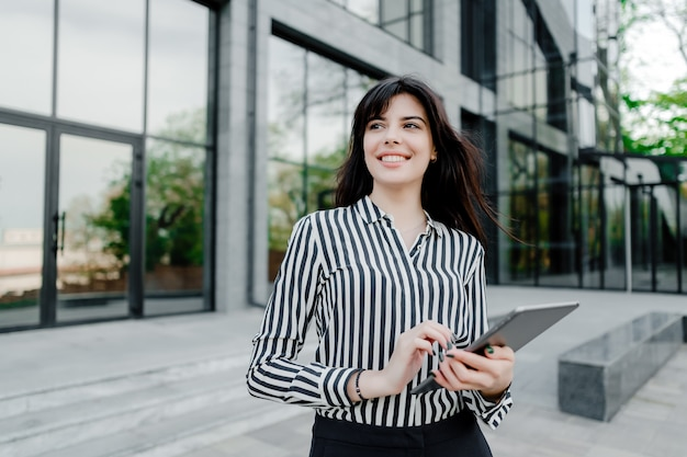 Femme, utilisation, tablette, dehors, bâtiment entreprise Photo Premium