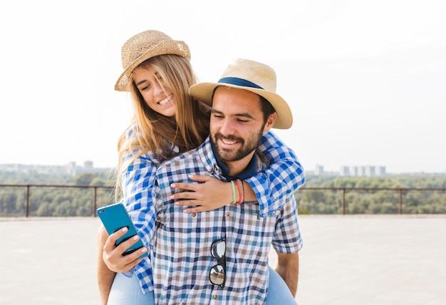 Femme, utilisation, téléphone portable, tout, avoir, sur, dos, petit ami Photo gratuit