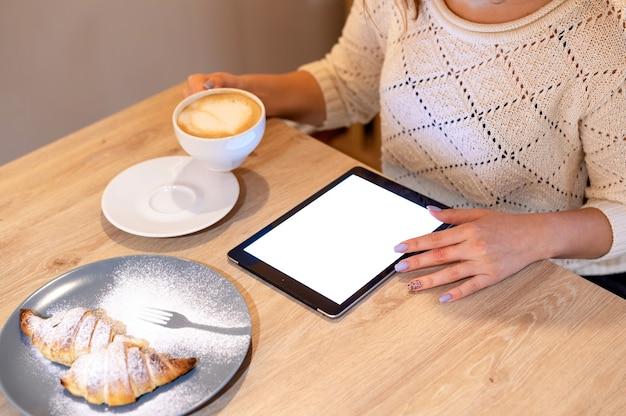 Une Femme Utilise Une Tablette Tenant Une Tasse De Café, Dessert Sur Une Table En Bois Photo gratuit