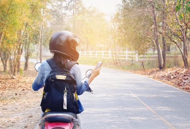 Femme utilise le téléphone et la moto en bordure de route. Photo Premium